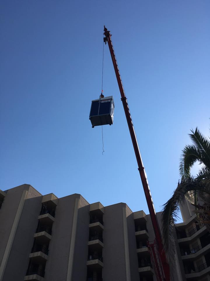 Portable toilet unit being lifted up by a crane