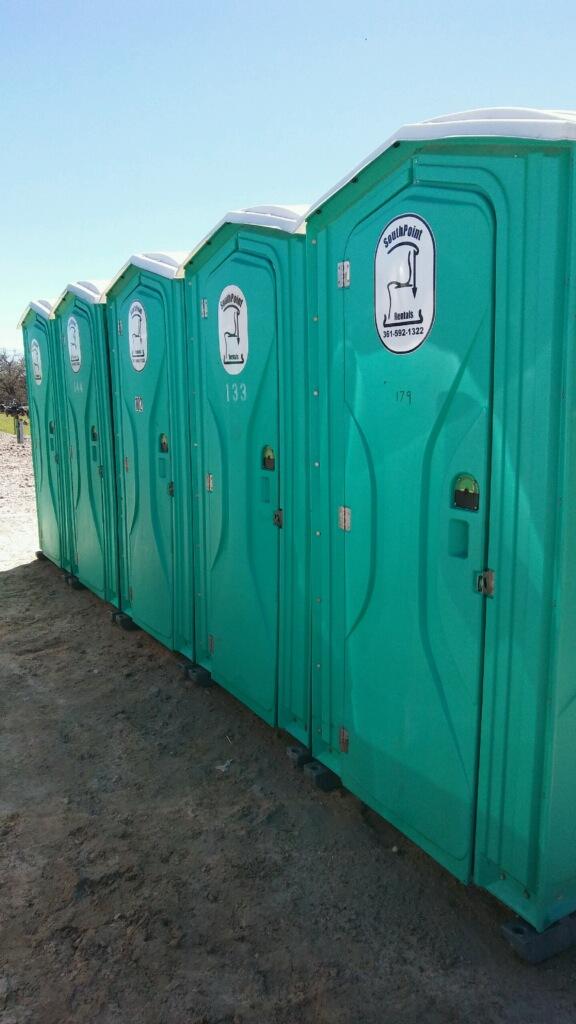 Five cyan-colored portable toilet units
