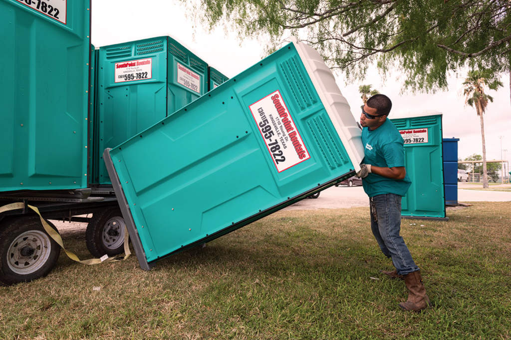 Loading a portable restroom onto a truck trailer