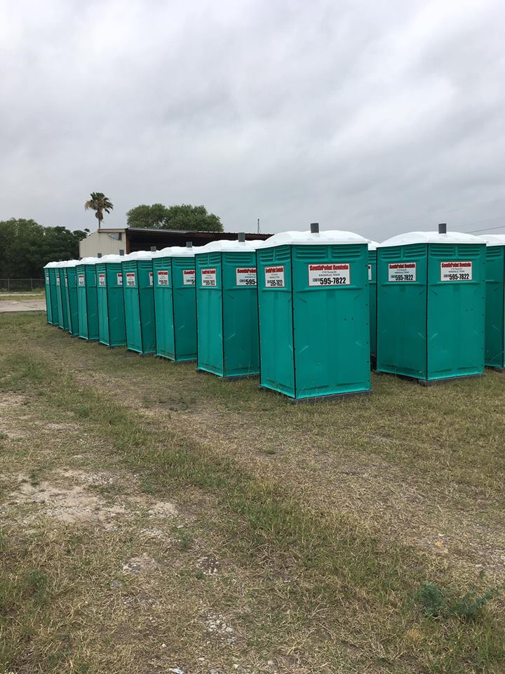 Rows of cyan-colored portable restrooms